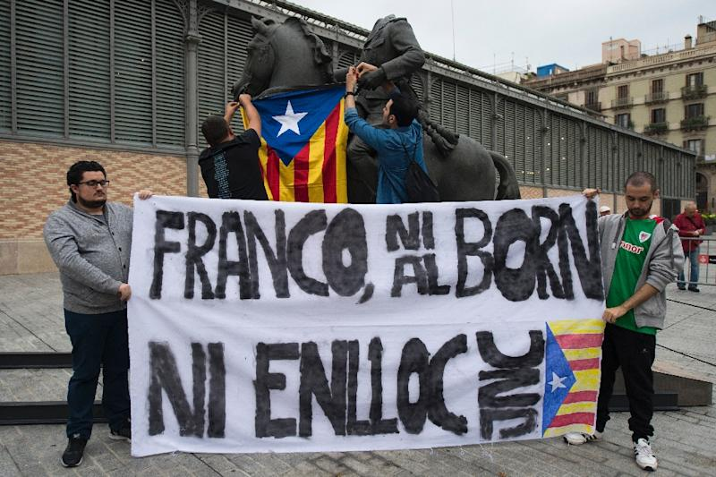 Protestors hang a Catalan Pro-independence flag on a headless sculpture of Francisco Franco riding a horse during the unveiling of the statue