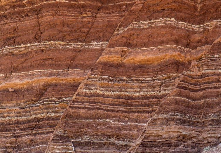The side of rocks showing lines of different types of rock and fault lines.