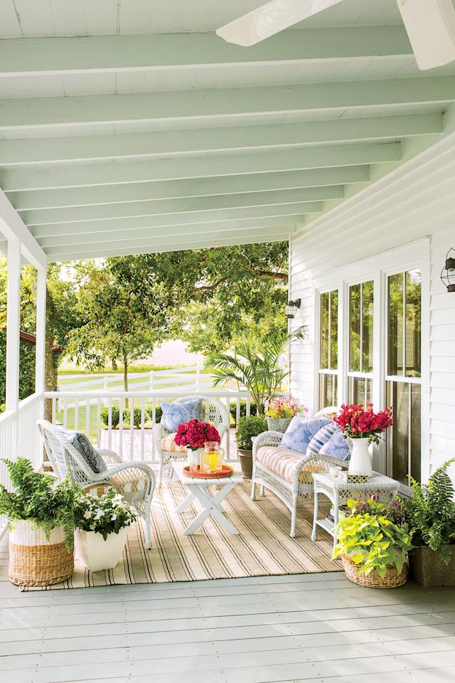 <p>Clusters of baskets and pots filled with plants adds low-to-the-ground greenery and color for a polished porch look.</p>