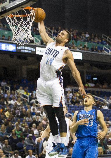 Charlotte Bobcats' Jeff Taylor (44) dunks of the fast break with Dallas Mavericks' Gal Mekel (33) trailing in first half of a preseason NBA game at the Greensboro Coliseum in Greensboro, N.C., Saturday, Oct. 19, 2013. (AP Photo/Lynn Hey)