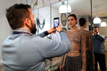 French designer Julien Fournie (L) takes pictures of model Greta (R) during a fitting at his workshop ahead of his Spring-Summer 2018 Haute Couture fashion show presentation in Paris, France, January 15, 2018. Picture taken January 15, 2018.  REUTERS/Charles Platiau