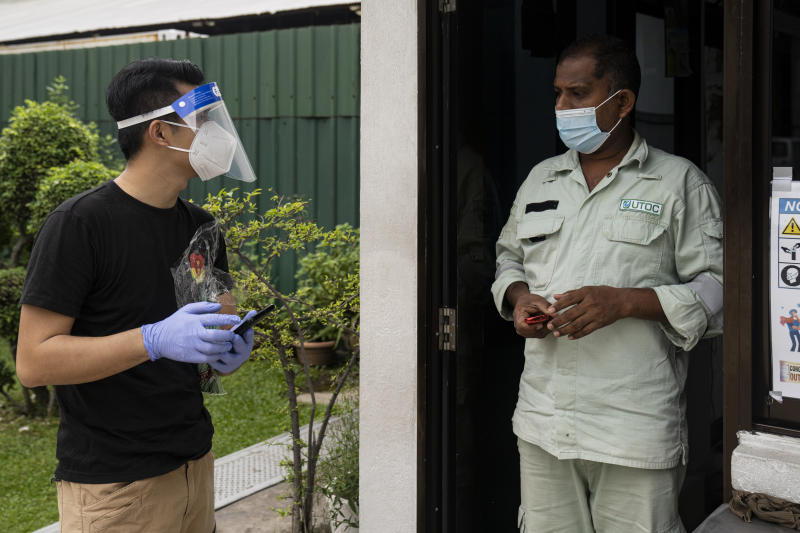 SINGAPORE, SINGAPORE - MAY 23: A volunteer wearing protective face mask talks to a security guard at a factory converted dormitory on May 23, 2020 in Singapore. This reassurance operation is an initiative by Covid-19 Migrant Support Coalition, a non-governmental group in Singapore.(Photo by Ore Huiying/Getty Images)
