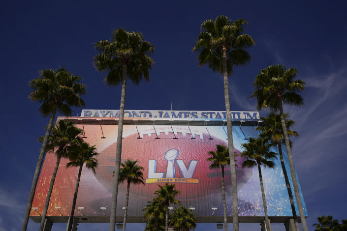 A sign for Super Bowl 55 is framed by palm trees at Raymond James Stadium Thursday, Feb. 4, 2021, in Tampa, Fla. The city is hosting Sunday's Super Bowl football game between the Tampa Bay Buccaneers and the Kansas City Chiefs. (AP Photo/Charlie Riedel)