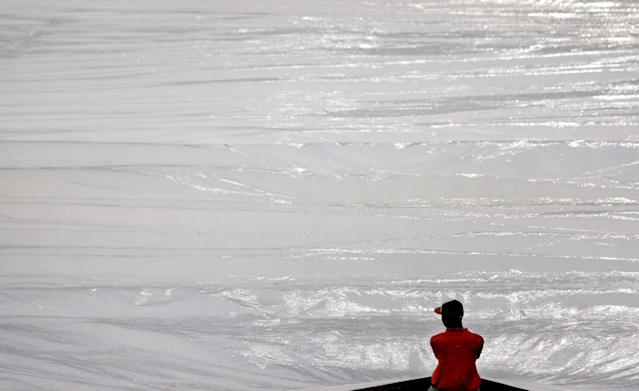 A groundskeeper pulls a tarp into place over the infield during a rain delay in a baseball game between the Baltimore Orioles and the Boston Red Sox, Tuesday, June 10, 2014, in Baltimore. (AP Photo/Patrick Semansky)