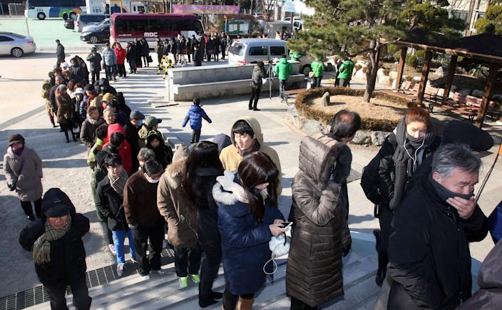 South Koreans wait in line to cast their votes in a presidential election at a polling station in Seoul, South Korea, Wednesday, Dec. 19, 2012. Huge crowds turned out Wednesday to vote in the tight presidential race pitting the son of North Korean refugees against the conservative daughter of a late dictator. (AP Photo/Yonhap, Kim Ju-sung) KOREA OUT