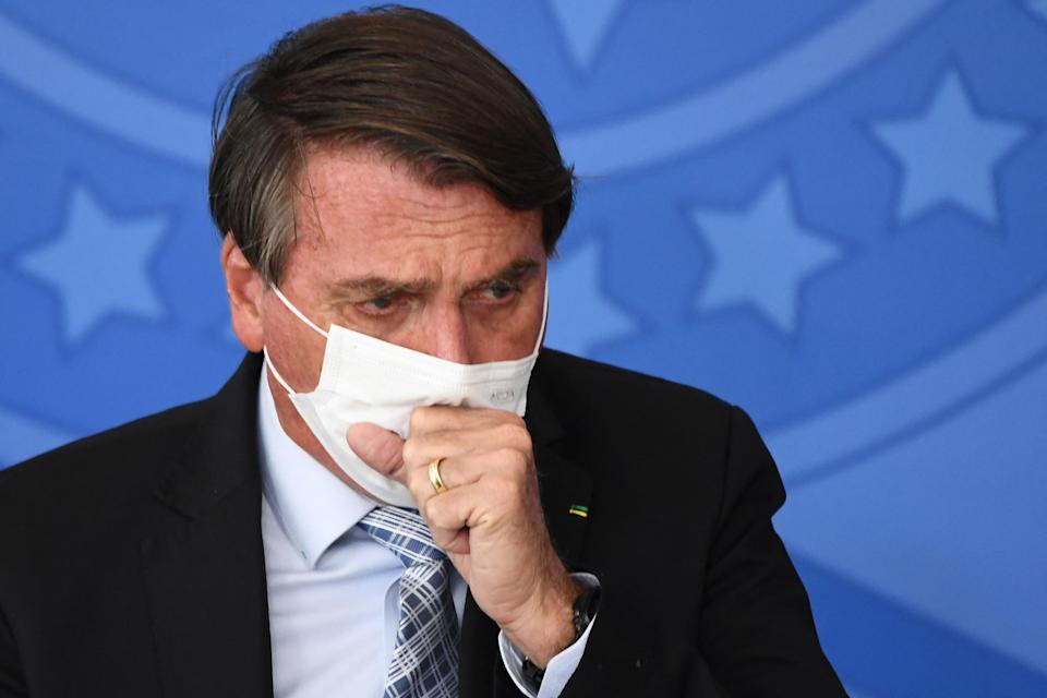 Brazilian President Jair Bolsonaro coughs during the sanction of the law that authorizes states, municipalities and the private sector to buy vaccines against COVID-19, at the Planalto Palace in Brasilia, on March 10, 2021. - Until now, with more than 260,000 deaths by the coronavirus, only the federal Government was authorized to buy vaccines. (Photo by EVARISTO SA / AFP) (Photo by EVARISTO SA/AFP via Getty Images)