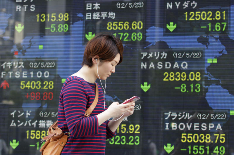 A women walks past an electronic stock indicator in Tokyo Wednesday, May 23, 2012. Japan's Nikkei 225 index fell 1.98 percent to 8,556.60 as a report that Greece is considering preparations to leave the euro common currency sent Asian stock markets lower Wednesday. (AP Photo/Shizuo Kambayashi)