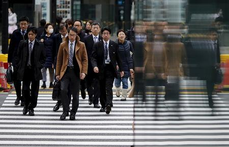 People are reflected on a wall as they cross a road at Tokyo's business district, Japan, February 22, 2016. REUTERS/Toru Hanai/Files