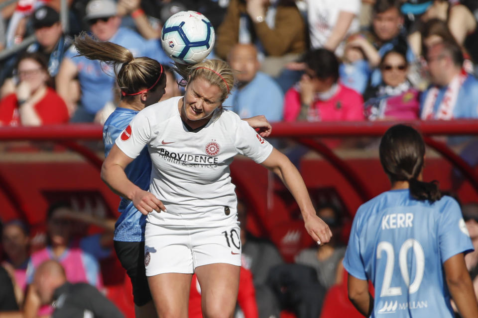 Portland Thorns FC midfielder Lindsey Horan, center, goes for a header against Chicago Red Stars midfielder Morgan Brian, left, during the first half of an NWSL playoffs semi-final soccer match Sunday, Oct. 20, 2019, in Bridgeview, Ill. (AP Photo/Kamil Krzaczynski)