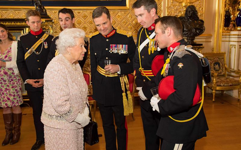 Queen Elizabeth II meets members of The Royal Lancers during a reception following the ceremonial presentation of the Guidon to The Royal Lancers at Windsor Castle - Credit: DOMINIC LIPINSKI/AFP