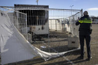 A police officer takes images of a torched coronavirus testing facility in the Dutch fishing village of Urk, Sunday, Jan. 24, 2021, after it was torch Saturday night by rioting youths protesting on the first night of a nation-wide curfew. (AP Photo/Peter Dejong)