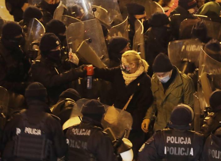 Police use tear gas against an opposition lawmaker, Barbara Nowacka, as protesters block a major thoroughfare in Warsaw, Poland, Saturday Nov. 28, 2020. The police blocked protesters from marching in Warsaw as demonstrations took place across Poland against an attempt to restrict abortion rights and recent use of force by police. (AP Photo/Czarek Sokolowski)