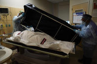 Transporters Miguel Lopez, right, Noe Meza prepare to move a body of a COVID-19 victim to a morgue at Providence Holy Cross Medical Center in the Mission Hills section of Los Angeles on Saturday, Jan. 9, 2021. (AP Photo/Jae C. Hong)