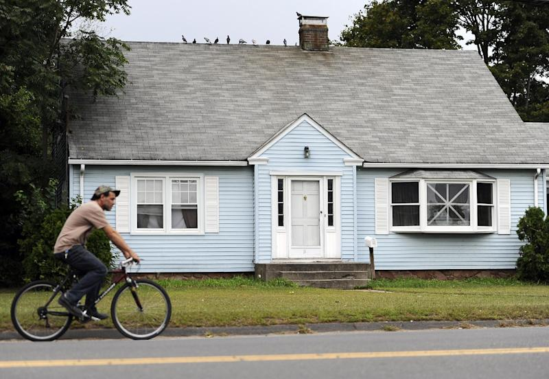 A man rides a bicycle by a house owned by the uncle of former New England Patriot's Aaron Hernandez, Thursday, Sept. 12, 2013 in Bristol, Conn. A group of people who all have ties to a small blue cape-style home in Bristol have become central figures in the investigations linking former New England Patriot Aaron Hernandez to two murder cases. (AP Photo/Jessica Hill)
