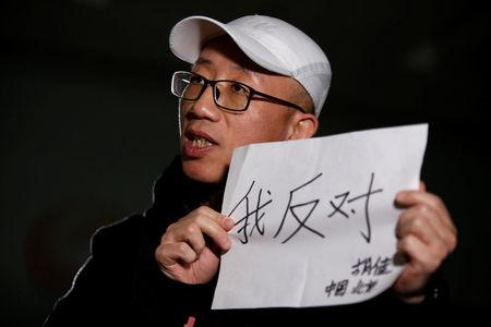 """Chinese activist Hu Jia holds a paper as he speaks during an interview with Reuters in Beijing, China February 28, 2018. Picture taken February 28, 2018. The Chinese characters read, """"I object"""". REUTERS/Thomas Peter"""