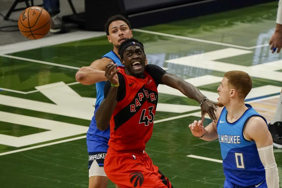 Toronto Raptors' Pascal Siakam is fouled by Milwaukee Bucks' D.J. Augustin during the first half of an NBA basketball game Thursday, Feb. 18, 2021, in Milwaukee. (AP Photo/Morry Gash)