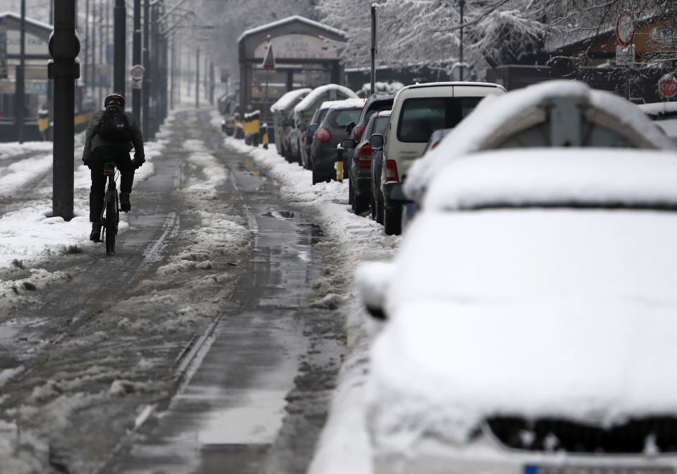 A man rides a bicycle through the snow covered street in Belgrade, Serbia, Monday, Jan. 11, 2021. A spate of rainy and snowy weather across the Balkans in the past days has left homes and fields flooded, disrupted road and sea traffic and caused power outages. (AP Photo/Darko Vojinovic)