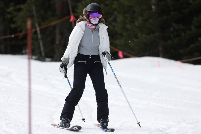 FILE - In this May 27, 2020, file photo, a skier wears a face covering while negotiating the slope at the reopening of Arapahoe Basin Ski Resort, which closed in mid-March to help in the effort to stop the spread of the new coronavirus, in Keystone, Colo. Roughly seven months after the coronavirus cut the ski season short at the height of spring break, resorts across the U.S. and Canada are slowly picking up the pieces and figuring out how to safely reopen this winter. (AP Photo/David Zalubowski, File)