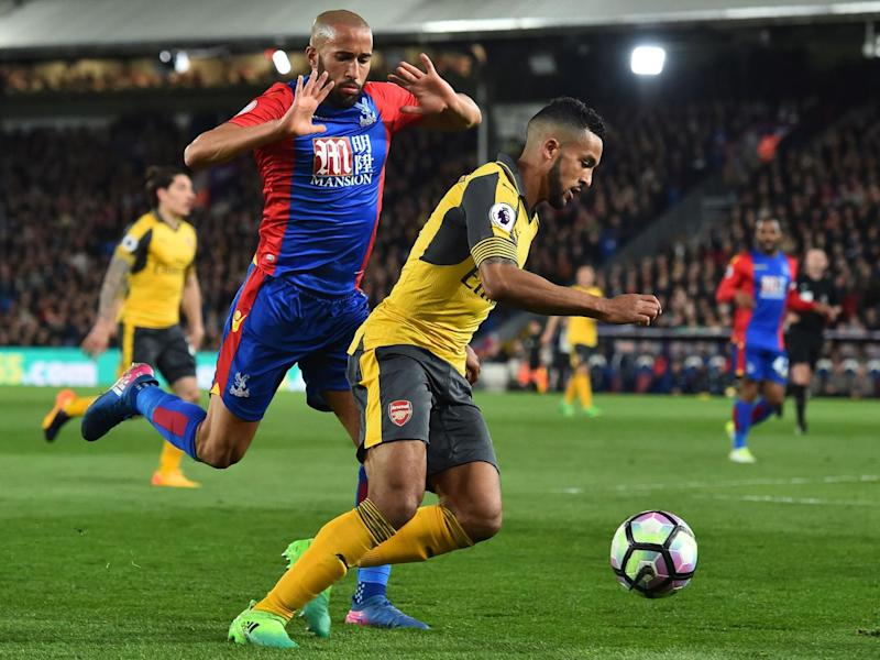 Walcott attempts to take the ball past Townsend (Getty)