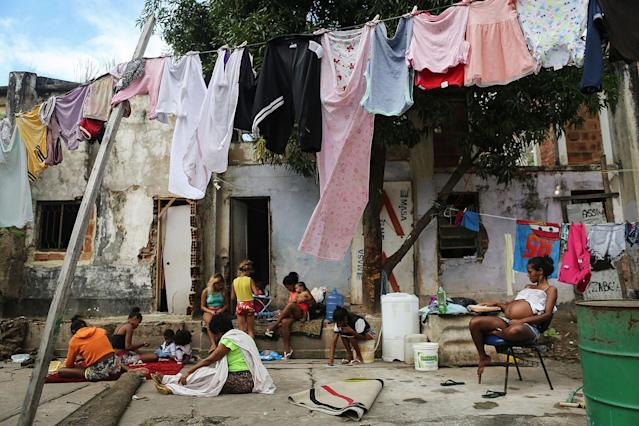 <p>Residents of the Mangueira favela sit outside their homes in Rio de Janeiro, May 2, 2017. (Photo: Mario Tama/Getty Images) </p>