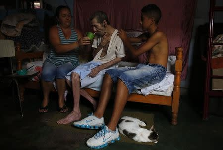 Cerebrovascular accident (CVA) patient Pedro, drinks water with the help of his daughter Daniela (L), 38, inside their house in Brasilandia slum, of which they are without water for 13 hours a day, in Sao Paulo February 11, 2015. REUTERS/Nacho Doce