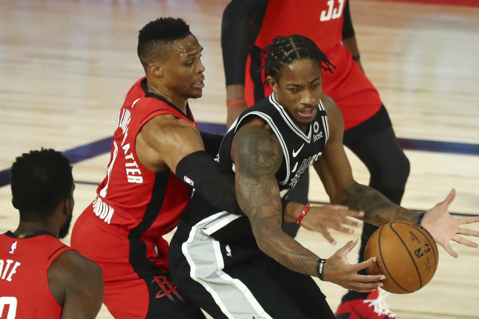 Houston Rockets guard Russell Westbrook (0), left, reaches for the ball in between the hands of San Antonio Spurs forward DeMar DeRozan (10), right, during the first half of an NBA basketball game Tuesday, Aug. 11, 2020, in Lake Buena Vista, Fla. (Kim Klement/Pool Photo via AP)