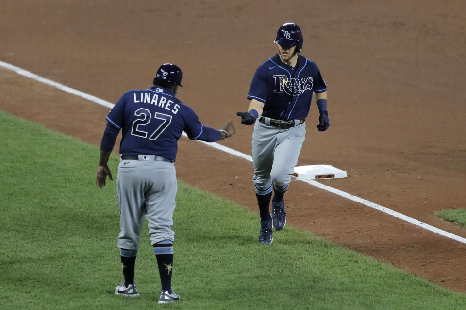 Tampa Bay Rays' Michael Brosseau, right, runs by third base coach Rodney Linares after hitting a solo home run off Baltimore Orioles starting pitcher Wade LeBlanc during the sixth inning of a baseball game, Saturday, Aug. 1, 2020, in Baltimore. (AP Photo/Julio Cortez)