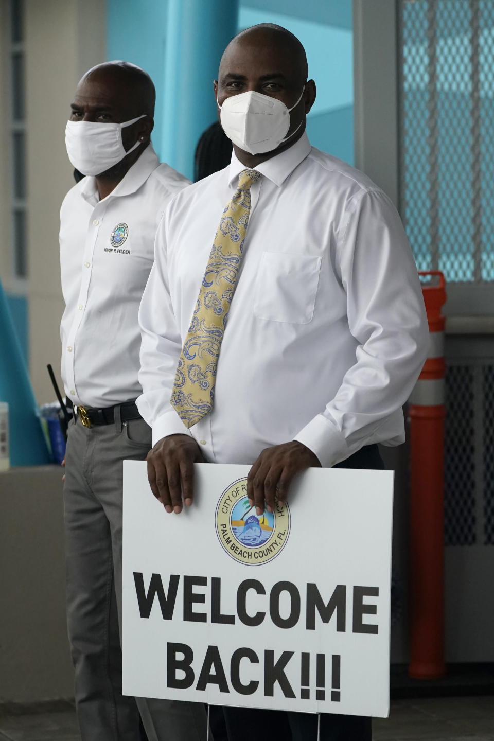 Riviera Beach, Fla. City Councilman Tradrick McCoy holds a sign welcoming students as he stands with Mayor Ronnie L. Felder, Tuesday, Aug. 10, 2021, during the first day of school at Washington Elementary School in Riviera Beach in Palm Beach County. (AP Photo/Wilfredo Lee)