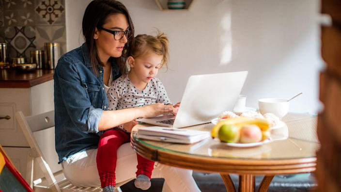 Photo of a little girl trying to help mom who is working on a computer at their dining table.