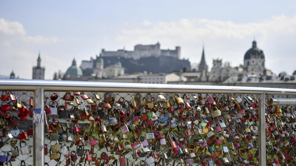 Looks hang on the fence of the Makartsteg in Salzburg, Austria, Friday, April 3, 2020. The Austrian government has moved to restrict freedom of movement for people, in an effort to slow the onset of the COVID-19 coronavirus. (AP Photo/Kerstin Joensson)