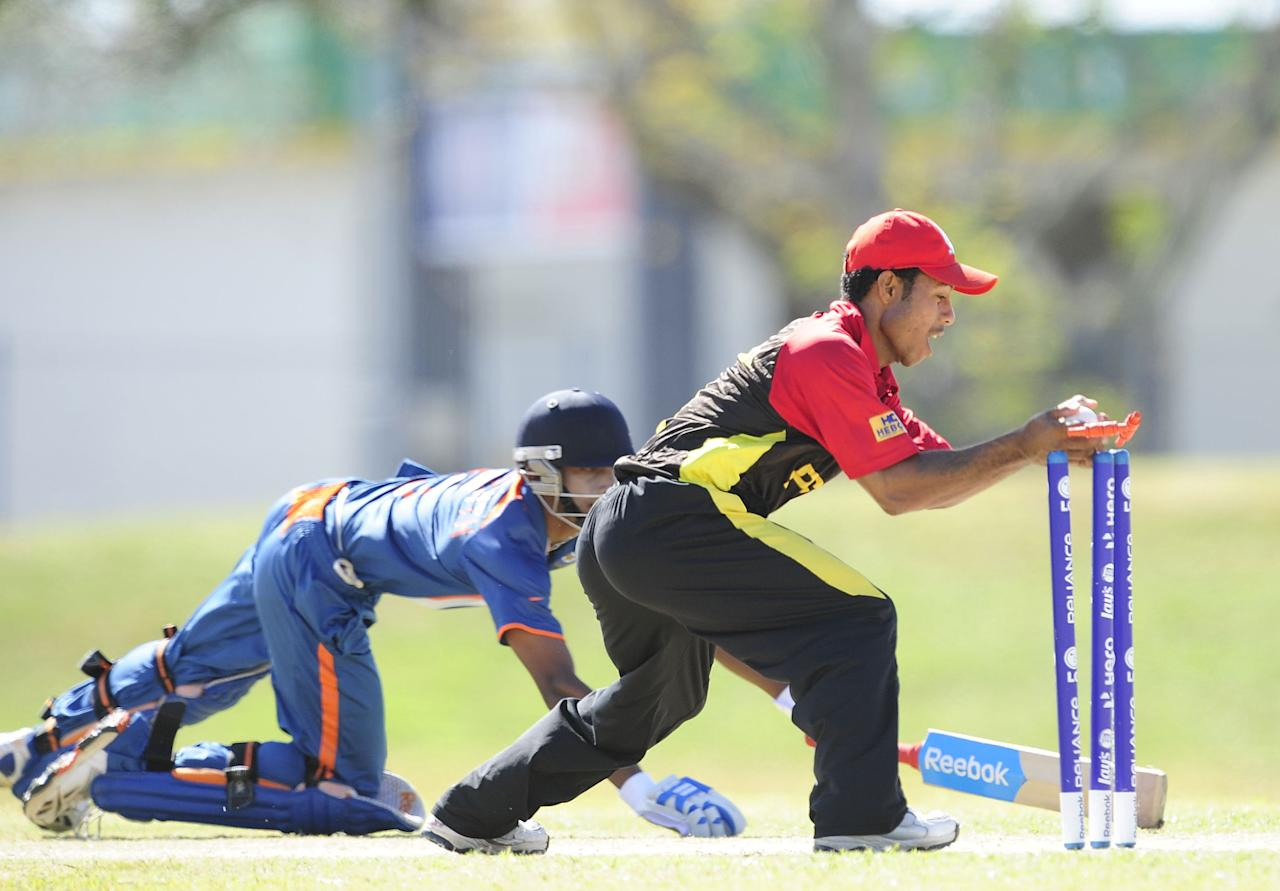 TOWNSVILLE, AUSTRALIA - AUGUST 16:  Sese Bau of Papua New Guniea runs out Baba Aparajith of India  during the ICC U19 Cricket World Cup 2012 match between India and PNG at Endeavour Park on August 16, 2012 in Townsville, Australia.  (Photo by Ian Hitchcock-ICC/Getty Images)