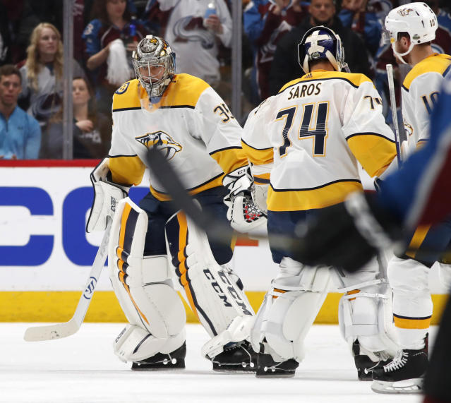Nashville Predators goaltender Pekka Rinne, left, skates back to the team box as he is replaced by backup goaltender Juuse Saros after giving up a goal to Colorado Avalanche center Nathan MacKinnon in the second period of Game 3 of an NHL hockey first-round playoff series Monday, April 16, 2018, in Denver. (AP Photo/David Zalubowski)