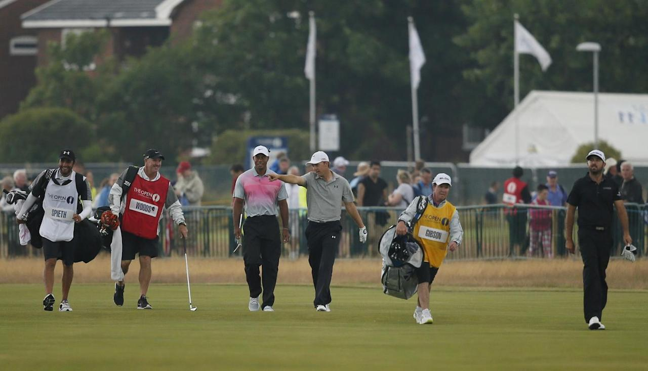 Tiger Woods of the US, center left, walks along the 18th fairway with Jordan Spieth of the US, center right, and Rhein Gibson of Australia, right, during the third day of the British Open Golf championship at the Royal Liverpool golf club, Hoylake, England, Saturday July 19, 2014. (AP Photo/Alastair Grant)