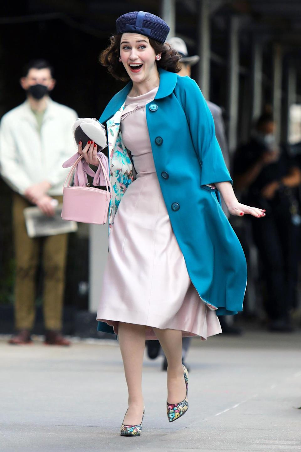 <p>Brosnahan sported a bright turquoise coat, a pale pink dress and a huge smile on set on May 17. </p>