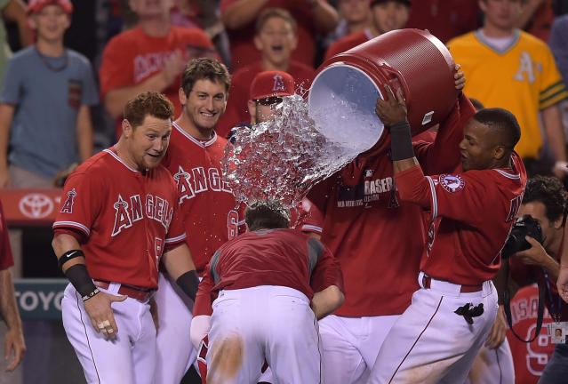 Los Angeles Angels team members douse Collin Cowgill, below, with liquid after he hit a home run to win the game in the 14th inning of a baseball game against the Oakland Athletics, Tuesday, June 10, 2014, in Anaheim, Calif. (AP Photo/Mark J. Terrill)