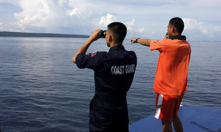 Philippine Coast Guard coast guard officers scan the horizon for survivors off Burias Island on June 15, 2013