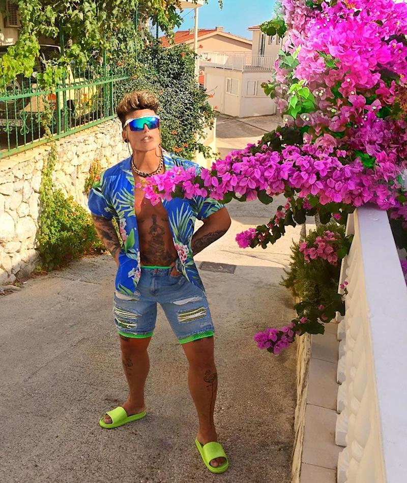 A photo of Neven Ciganovic from Zagreb, Croatia, wearing an Hawaiian shirt and denim cut-off shorts with neon green pool slides