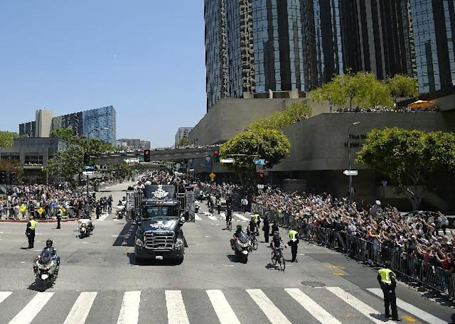 Members of the Los Angeles Kings, hold up the Stanley Cup trophy while riding in a parade through downtown Los Angeles, Monday, June 16, 2014. The parade and rally were held to celebrate the Los Angeles Kings' second Stanley Cup championship in three seasons. (AP Photo/Mark J. Terrill)