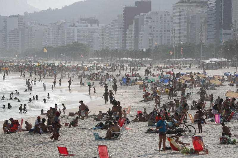 People relax on Leme beach on a sunny day in Rio de Janeiro, Brazil.