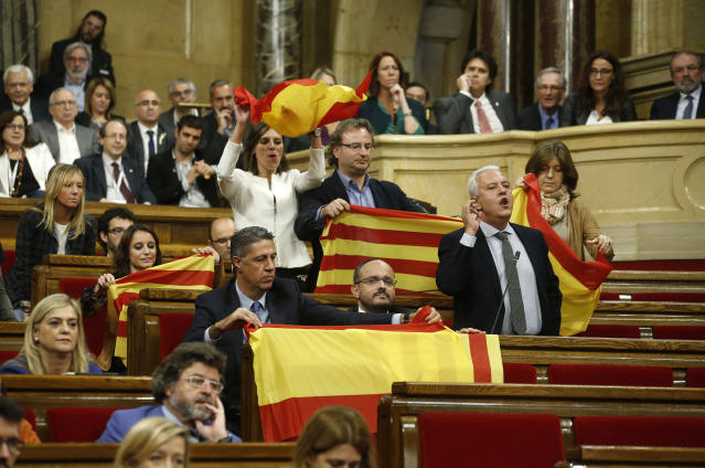 <p>Opposition Catalan lawmakers hold Spanish national flags and Estelada's before leaving the chamber to boycott a vote on independence inside the Catalan parliament in Barcelona, Spain, Friday, Oct. 27, 2017. (Photo: Manu Fernandez/AP) </p>