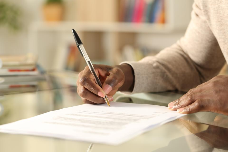 Close up of black man hands signing document on a desk at home