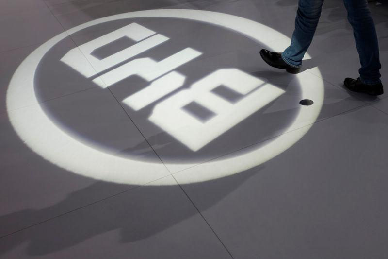 FILE PHOTO: A man walks past a light flashing on the floor in the shape of the logo of BYD Auto during the media preview of the 10th China International Automobile Exhibition in Guangzhou