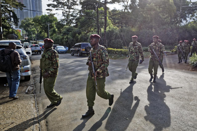 Security forces walk to the scene as continued blasts and gunfire could be heard early Wednesday, Jan. 16, 2019 in Nairobi, Kenya. Extremists stormed a luxury hotel in Kenya's capital on Tuesday, setting off thunderous explosions and gunning down people at cafe tables in an attack claimed by Africa's deadliest Islamic militant group. (AP Photo/Ben Curtis)