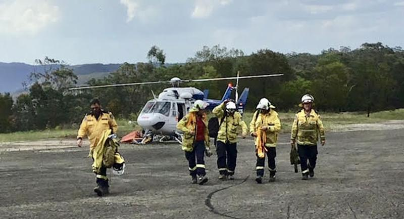 NSW Rural Fire Services firefighters are pictured next to a helicopter.