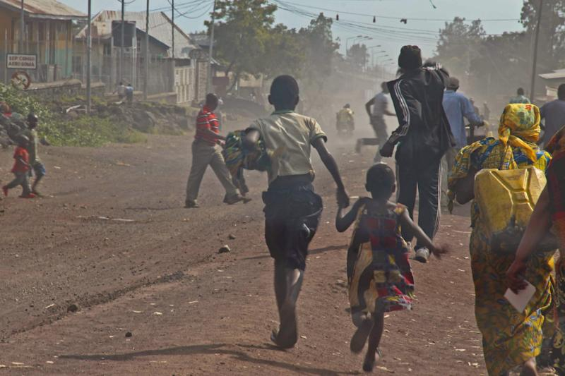 People flee as fighting erupts between the M23 rebels and Congolese army near the airport at Goma, Congo, Monday, Nov. 19, 2012. Rebels believed to be backed by Rwanda fired mortars and machine guns Monday in a village on the outskirts of the provincial capital of Goma and threatened to attack the city which is protected by ragtag Congolese government troops backed by United Nations peacekeepers. The gunfire and explosions erupted in the early afternoon, hours after the M23 rebels said they were halting fighting in order to negotiate with the government of Congo. (AP Photo/Melanie Gouby)