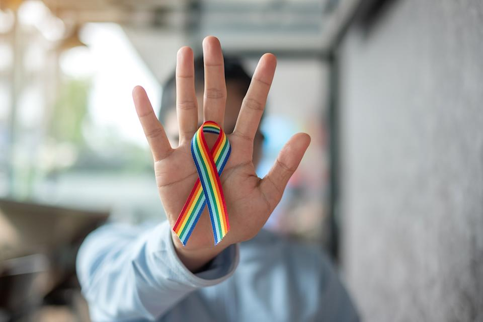 young woman with Rainbow ribbon LGBTQ for Lesbian, Gay, Bisexual, Transgender and Queer community pride concept