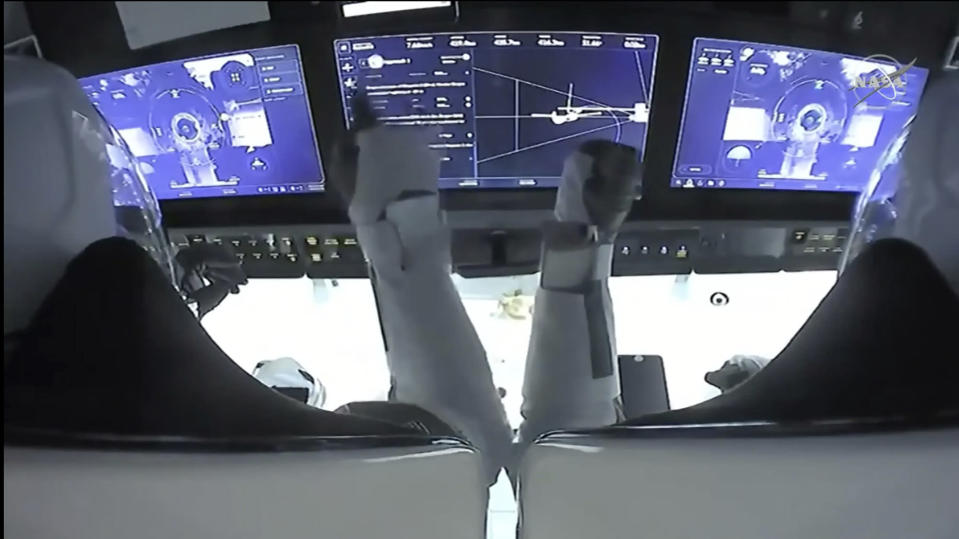 In this frame grab from NASA TV, astronauts Mike Hopkins, left, and Victor Glover monitor controls aboard SpaceX Dragon as the capsule approaches the International Space Station, late Monday, Nov. 16, 2020. (NASA TV via AP)