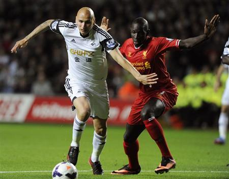Swansea City's Jonjo Shelvey (L) passes Liverpool's Mamadou Sakho before shooting to score a goal during their English Premier League soccer match at the Liberty Stadium, Swansea, Wales September 16, 2013. REUTERS/Rebecca Naden