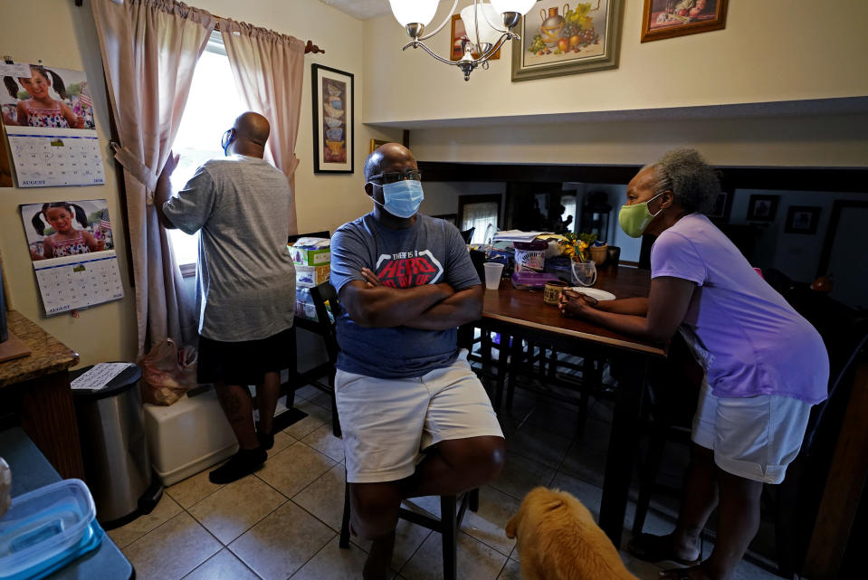 Larry Brown, left, talks with his parents John and Marilyn Brown as Larry cooks dinner, Thursday, Aug. 27, 2020, in Indianapolis. Larry doesn't know why his father's case was comparatively mild, as John Brown spent seven days on a ventilator _ about 40 less than his son. Marilyn ended up with a mild case. (AP Photo/Darron Cummings)