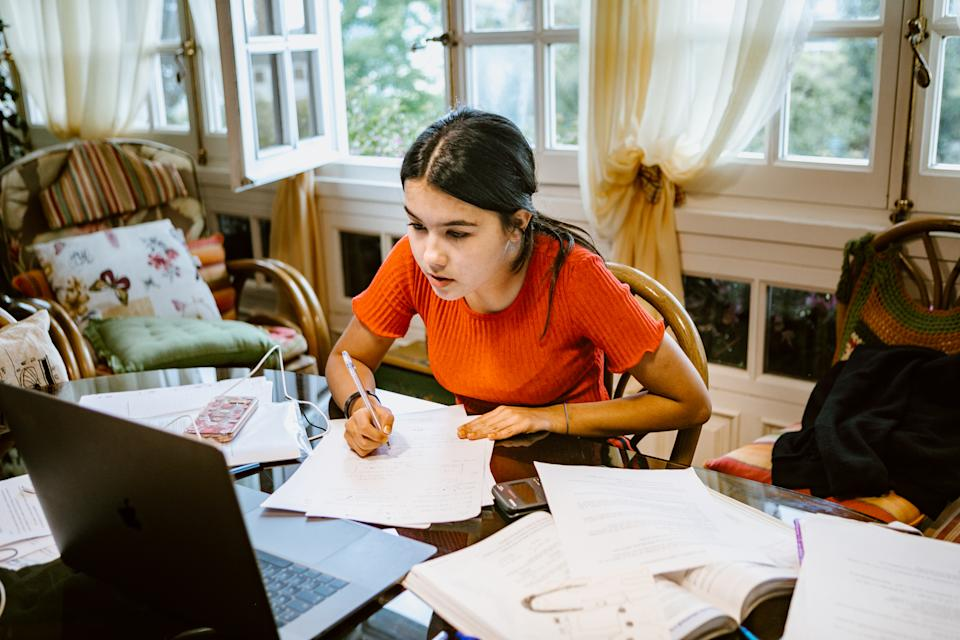 hispanic latina college student works on assignment in her dorm room. She is writing something in a notebook. A laptop is on her desk.